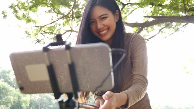 セルフスティックでスマートフォンで呼び出す若い女性のビデオ - 自画像点の映像素材/bロール