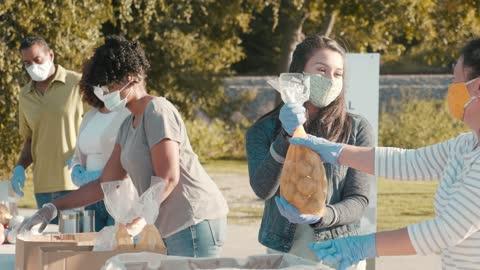 vídeos y material grabado en eventos de stock de mujer joven voluntaria con familia durante el remache de alimentos - voluntario