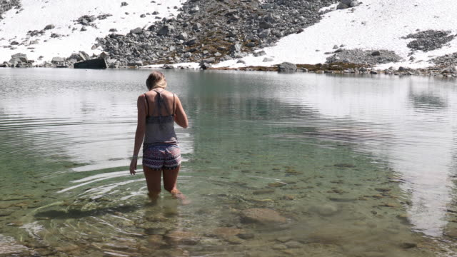 stockvideo's en b-roll-footage met young woman wades through alpine lake shallows, with smart phone - verfrissing