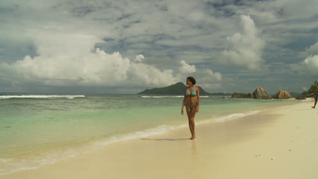 WS Young woman wading in ocean / Seychelles