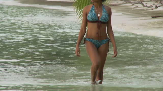 MS TU Young woman wading in ocean / Seychelles