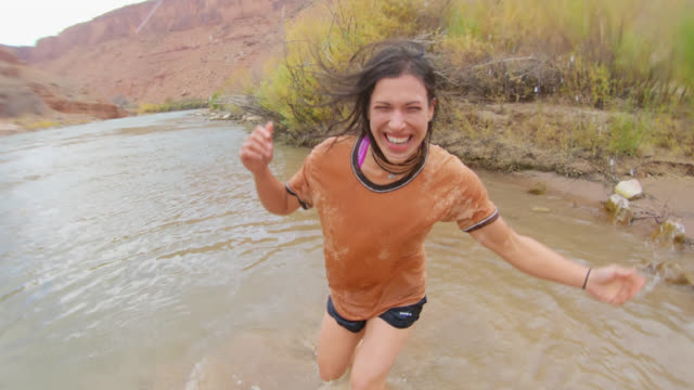 pov. young woman wading in river laughs and splashes at camera. - moab utah stock-videos und b-roll-filmmaterial