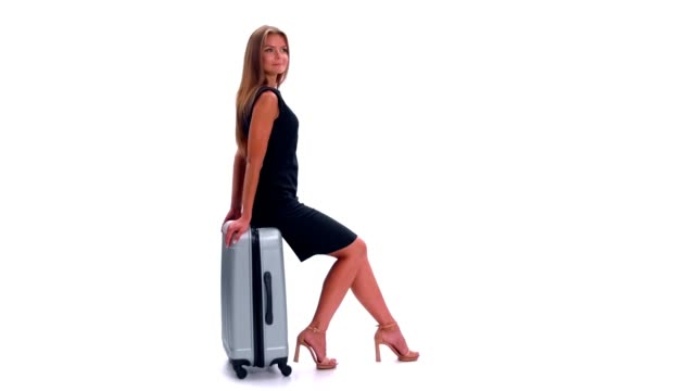 Young woman waiting and sitting on a suitcase