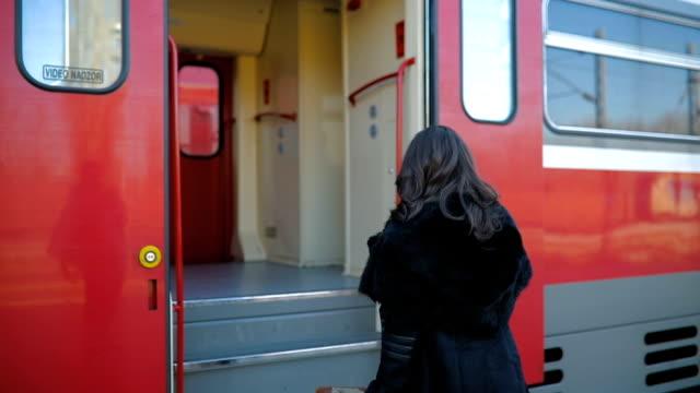 vídeos de stock e filmes b-roll de young woman waiting for a train at a station. train holidays - mala
