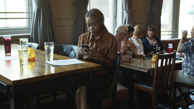young woman waiting for friends in pub - standing out from the crowd stock videos & royalty-free footage