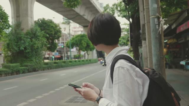 タクシーやユーバーを待っている若い女性 - 待つ点の映像素材/bロール