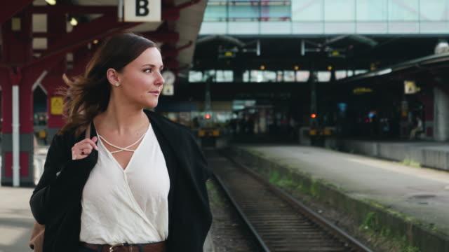 Ung kvinna väntar på tåget