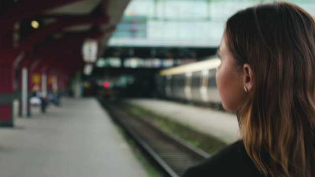 young woman waiting for the train - railway station stock videos and b-roll footage