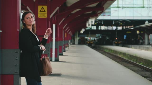 vídeos y material grabado en eventos de stock de mujer joven esperando el tren - estación de tren
