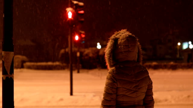 young woman waiting green sign to cross street at snowy evening - cold temperature stock videos & royalty-free footage