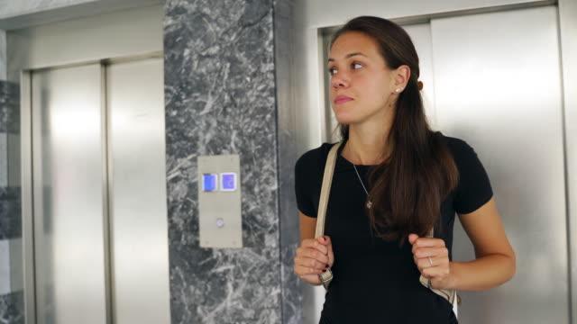 vídeos de stock e filmes b-roll de young woman waiting in front of elevator and looking around - esperar