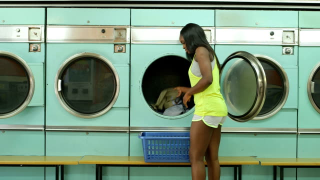 msl a young woman waits in a launderette - launderette stock videos and b-roll footage