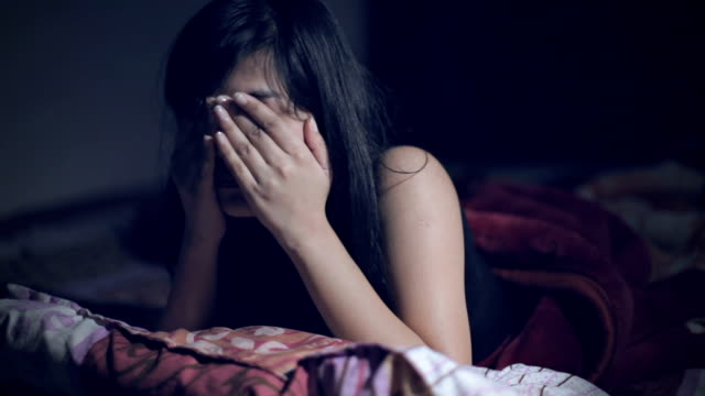 Young woman waking up at late night.