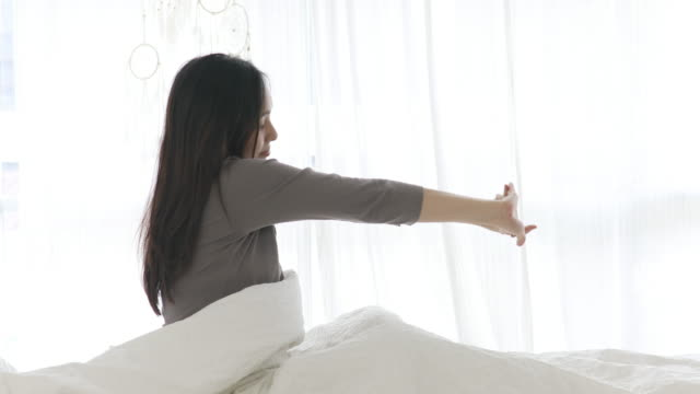 young woman waking up in white bed - only young women stock videos & royalty-free footage