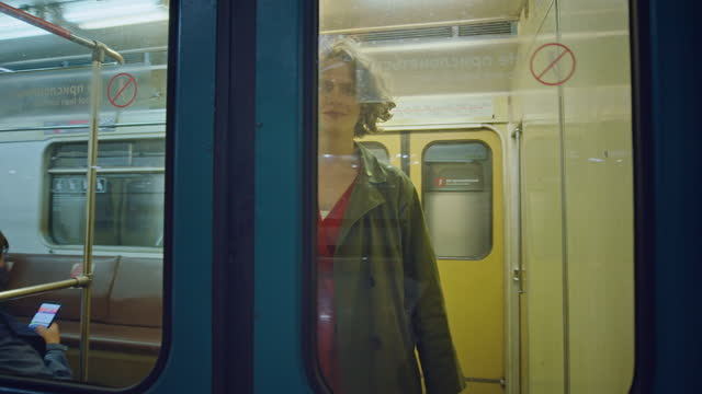 young woman walk into subway car, smile and wave - サウンドトラック点の映像素材/bロール