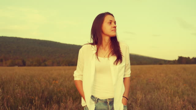 young woman walking across a meadow with hands in pockets - hands in pockets stock videos & royalty-free footage