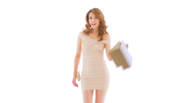 MS Young woman walking against white background with shopping bags and purse