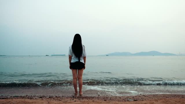 vídeos de stock, filmes e b-roll de jovem mulher caminhando sozinha na praia - ficando de pé