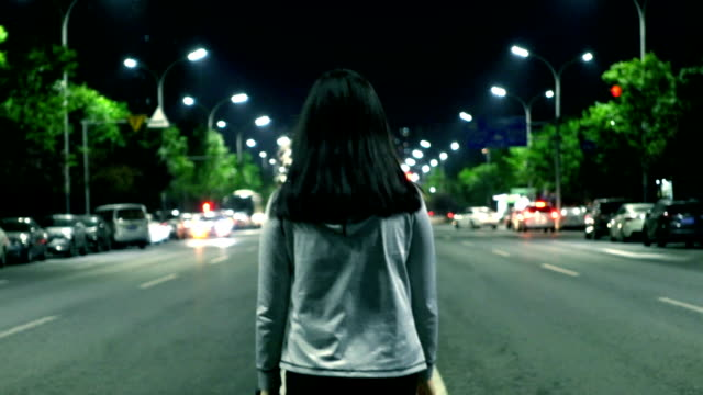 Young woman walking alone on the streets at night