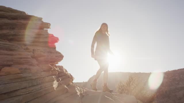 日の出崖に沿って歩いている若い女性 - 峡谷点の映像素材/bロール