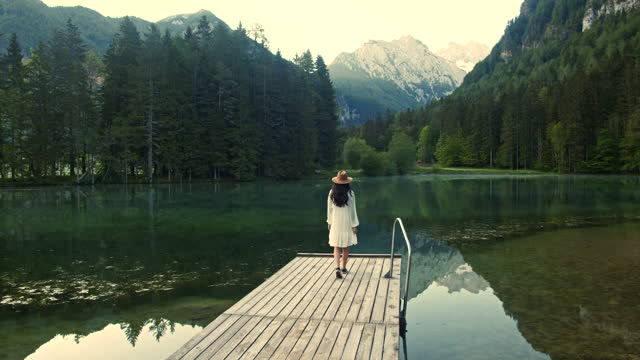 slow motion young woman walking along the wooden dock on the lake - slovenia stock videos & royalty-free footage