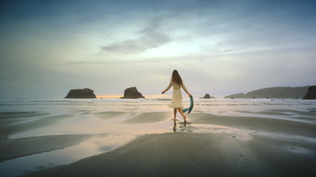 Young woman walking and twirling on Ocean Beach at Sunset