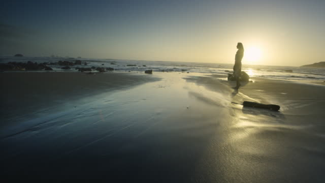 young woman walking and twirling on ocean beach at sunset - dress stock videos & royalty-free footage