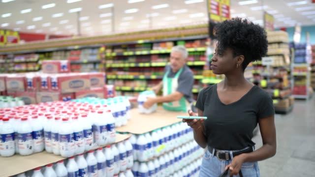 vídeos de stock, filmes e b-roll de mulher nova que anda e que usa o telefone móvel no supermercado - objeto manufaturado