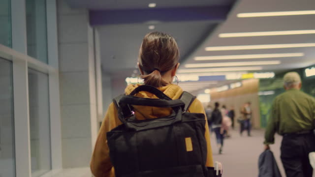 young woman walking at airport. - rucksack stock videos & royalty-free footage
