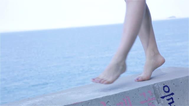 young woman walking at beach - 人の脚点の映像素材/bロール