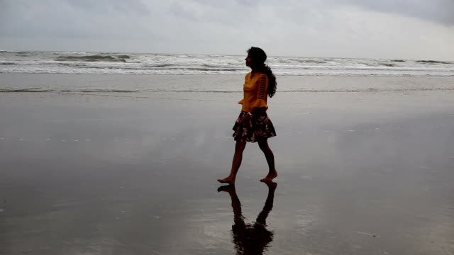 vidéos et rushes de jeune femme marchant sur la plage de morjim, goa - silhouette