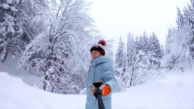 Junge Frau, die zu Fuß in der verschneiten Winterwald