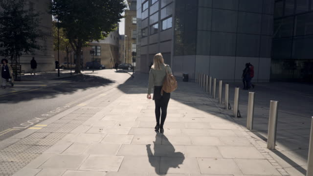 a young woman walking away from the camera. - borsetta video stock e b–roll