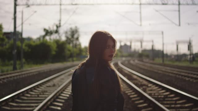 鉄道で離れて歩く若い女性。 - 人の背中点の映像素材/bロール