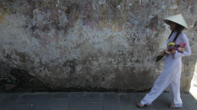 ws ld young woman walking by, holding flowers and wearing ao dai / hoi an, vietnam - traditionally vietnamese stock videos & royalty-free footage