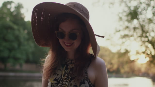 young woman walking by river, smiling - hüten stock-videos und b-roll-filmmaterial
