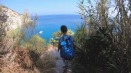 Young woman walking down stone stair path to a bay on Ponza Island coast cliff.