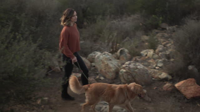WS Young woman walking her dog outdoors.