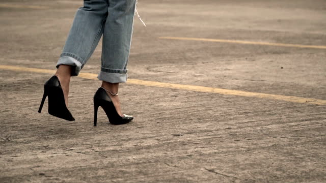 vídeos de stock e filmes b-roll de young woman walking high heel - jeans