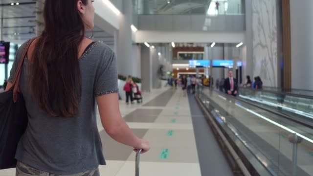 young woman walking in airport - airport terminal stock videos & royalty-free footage