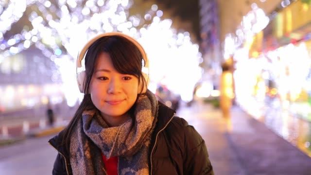 クリスマスの夜に買い物のための都市を歩く若い婦人 - 歯を見せて笑う点の映像素材/bロール