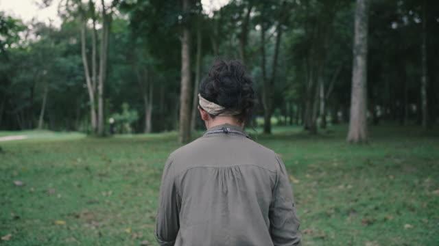 vídeos y material grabado en eventos de stock de joven mujer caminando en el bosque. - espalda humana