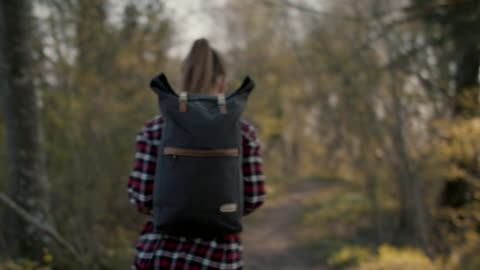stockvideo's en b-roll-footage met young woman walking in forest with backpack - rugzak