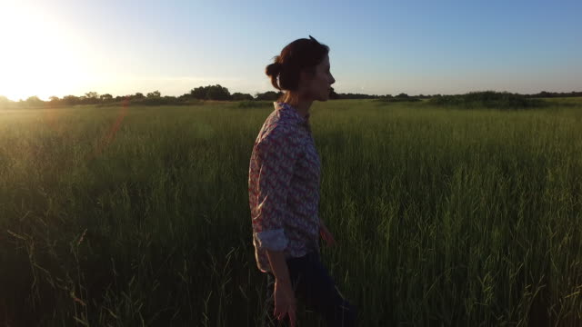 Young woman walking in green field
