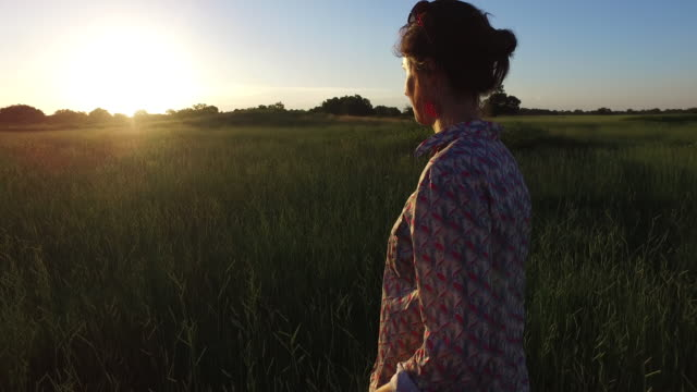 young woman walking in green field - ブラウス点の映像素材/bロール