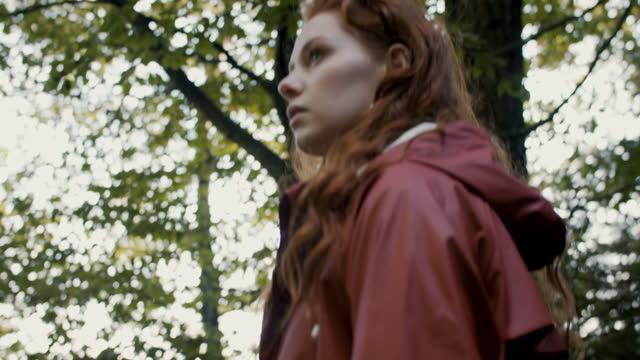 vidéos et rushes de young woman walking in lush forest - endroit isolé