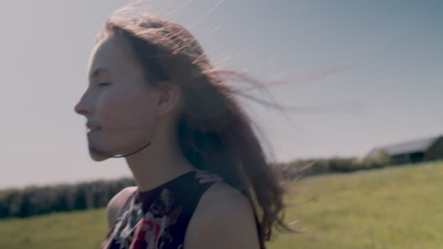 young woman walking in meadow - differential focus点の映像素材/bロール