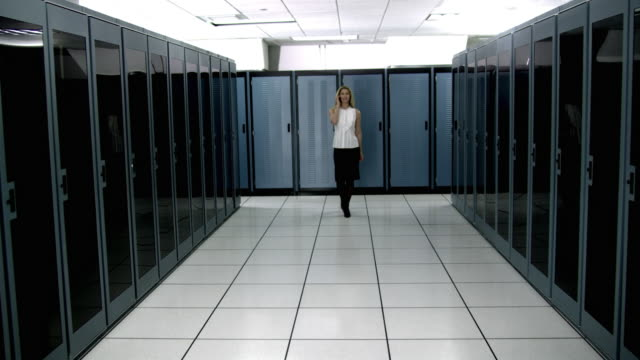 ws ds cu young woman walking in server room and talking on mobile phone - see other clips from this shoot 1480 stock videos and b-roll footage