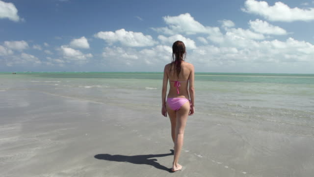 Young woman walking in shallow sea