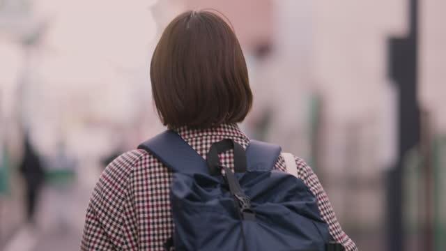 保護フェイスマスクを着用しながら通りを歩く若い女性 - 背中点の映像素材/bロール